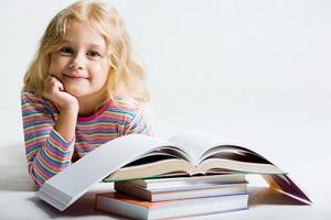 Девочка сидит перед книжками