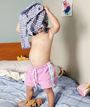 Ребёнок одевает футболку