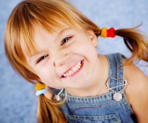 Девочка показывает зубы