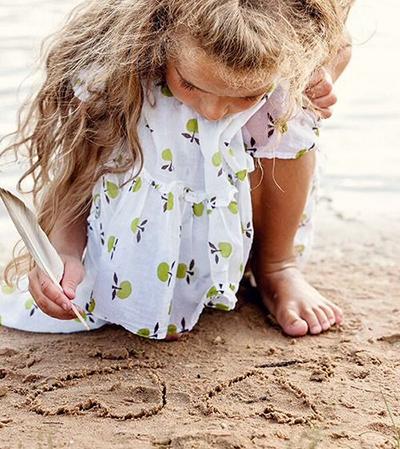 Девочка пишет пером по песку